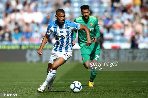 Steve Mounie of Huddersfield Town runs with the ball under pressure from Etienne Capoue of Watford during the Premier League match between...