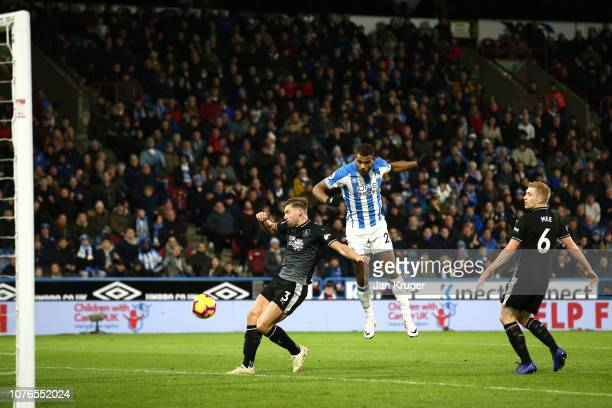 Steve Mounie of Huddersfield Town scores his sides first goal under pressure from Charlie Taylor of Burnley during the Premier League match between...