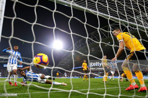 Steve Mounie of Huddersfield Town scores his team's first goal alongside Elias Kachunga during the Premier League match between Huddersfield Town and...