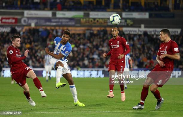 Steve Mounie of Huddersfield Town takes a shot under pressure from Andy Robertson of Liverpool during the Premier League match between Huddersfield...
