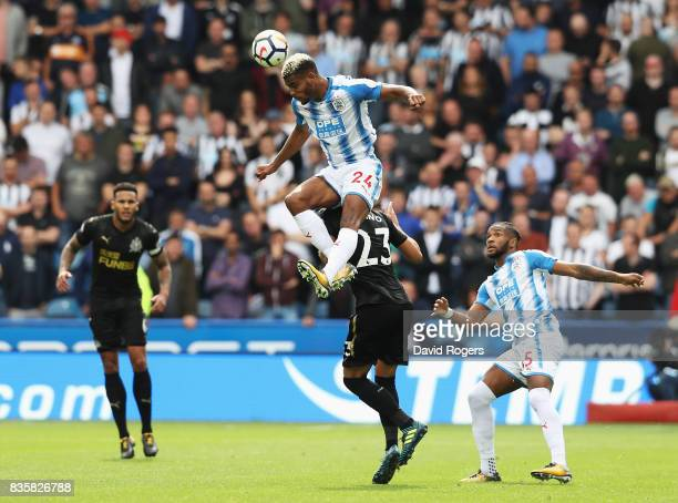 Steve Mounie of Huddersfield Town wins a header over Mikel Merino of Newcastle United during the Premier League match between Huddersfield Town and...