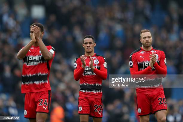 Steve Mounie Tom Ince and Laurent Depoitre of Huddersfield Town show appreciation to the fans following the Premier League match between Brighton and...