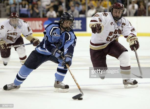 Steve Mullin of the Maine Blackbears takes the puck as Ben Eaves of the Boston College Eagles defends during the NCAA Frozen Four on April 8 2004 at...