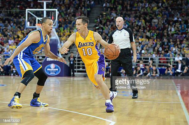 Steve Nash of the Los Angeles Lakers drives against Stephen Curry of the Golden State Warriors during the 2013 Global Games on October 15 2013 at the...