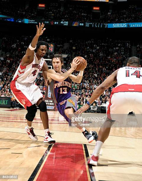 Steve Nash of the Phoenix Suns cuts through the lane defended by Chris Bosh of the Toronto Raptors on January 18, 2009 at the Air Canada Centre in...