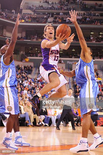 Steve Nash of the Phoenix Suns Drives against Juwan Howard of the Denver Nuggets in an NBA game played on October 11 at Indian Wells Tennis Garden in...