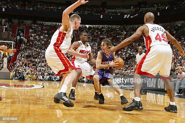 Steve Nash of the Phoenix Suns drives against Michael Doleac Keyon Dooling and Shandon Anderson of the Miami Heat on March 25 2005 at American...