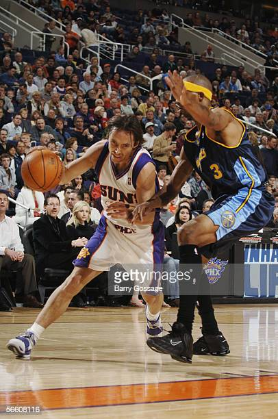 Steve Nash of the Phoenix Suns drives to the basket against DerMarr Johnson of the Denver Nuggets during the game at America West Arena on December 2...