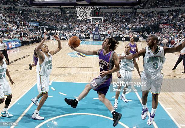 Steve Nash of the Phoenix Suns gets to the basket between Chris Paul and PJ Brown of the New Orleans/Oklahoma City Hornets during a NBA game on March...