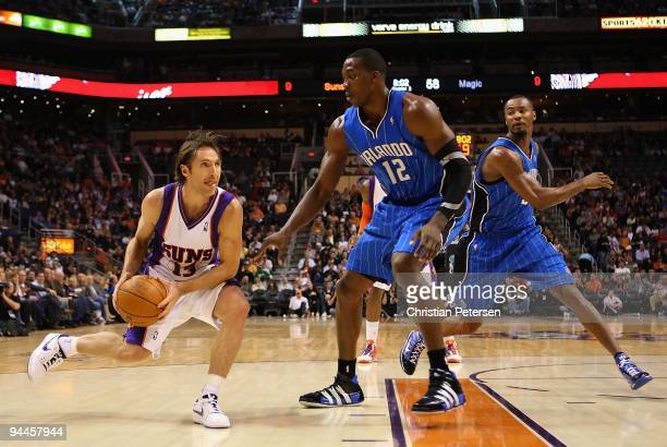 Steve Nash of the Phoenix Suns handles the ball under pessure from Dwight Howard of the Orlando Magic during the NBA game at US Airways Center on...