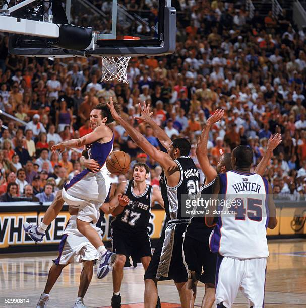 Steve Nash of the Phoenix Suns passes around Tim Duncan of the San Antonio Spurs in Game one of the Western Conference Finals during the 2005 NBA...
