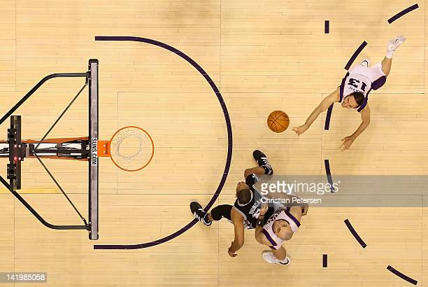 Steve Nash of the Phoenix Suns puts up a shot as Tim Duncan of the San Antonio Spurs blocks out Marcin Gortat during the NBA game at US Airways...