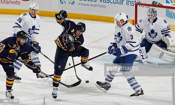 Steve Ott and Ville Leino of the Buffalo Sabres try to tip the puck in front of Dion Phaneuf and goaltender Jonathan Bernier of the Toronto Maple...