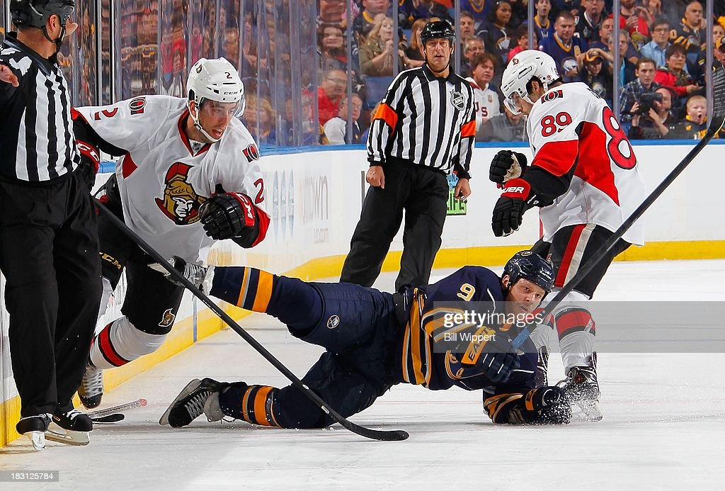Steve Ott #9 of the Buffalo Sabres is upended by Jared Cowen #2 and Cory Conacher #89 of the Ottawa Senators on October 4, 2013 at the First Niagara Center in Buffalo, New York.