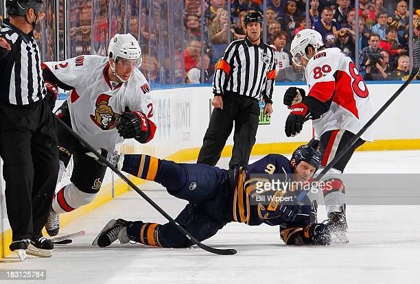 Steve Ott of the Buffalo Sabres is upended by Jared Cowen and Cory Conacher of the Ottawa Senators on October 4 2013 at the First Niagara Center in...