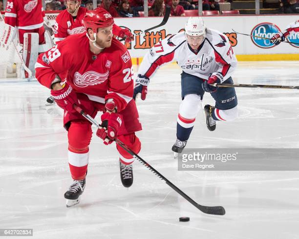 Steve Ott of the Detroit Red Wings skates up ice with the puck followed by T.J. Oshie of the Washington Capitals during an NHL game at Joe Louis...