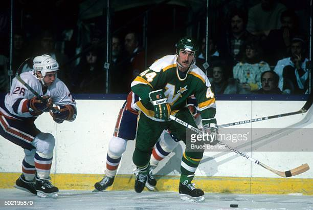 Steve Payne of the Minnesota North Stars skates with the puck as Pat Flately of the New York Islanders follows behind on January 7, 1986 at the...