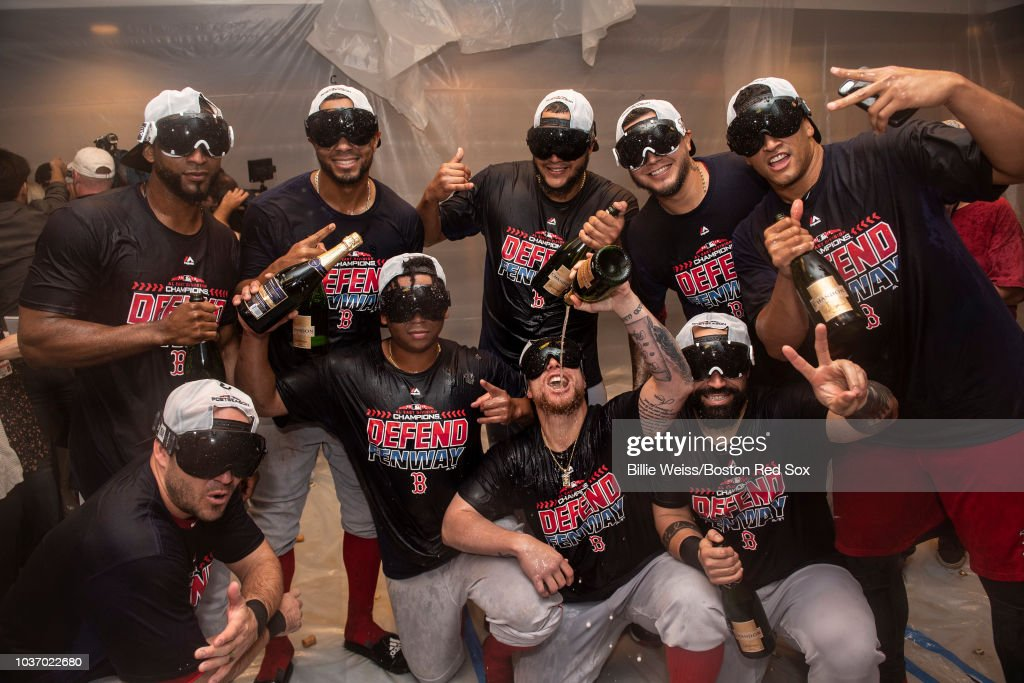 Steve Pearce #25, Eduardo Nunez #36, Xander Bogaerts #2, Rafael Devers #11, Christian Vazquez #7, Eduardo Rodriguez #57, Hector Velazquez #76, Sandy Leon #3, and William Cuevas #67 of the Boston Red Sox celebrate in the clubhouse after clinching the American League East division following a victory against the New York Yankees on September 20, 2018 at Yankee Stadium in the Bronx borough of New York City.