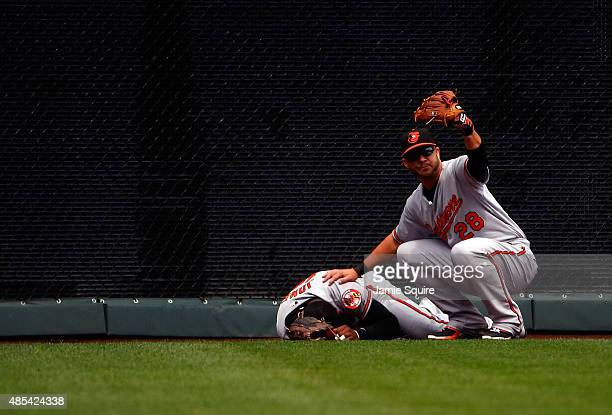 Steve Pearce of the Baltimore Orioles calls for help after Adam Jones hits the wall while trying to catch a fly ball during the 1st inning of the...