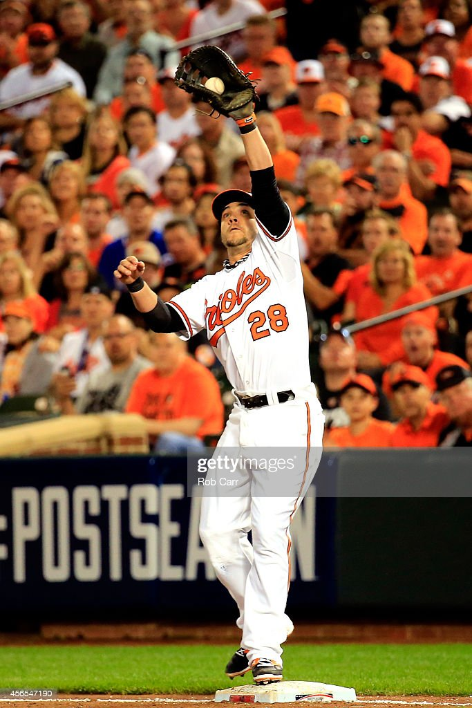 Steve Pearce #28 of the Baltimore Orioles catches a high throw at first base for the second out in the fifth inning against the Detroit Tigers during Game One of the American League Division Series at Oriole Park at Camden Yards on October 2, 2014 in Baltimore, Maryland.