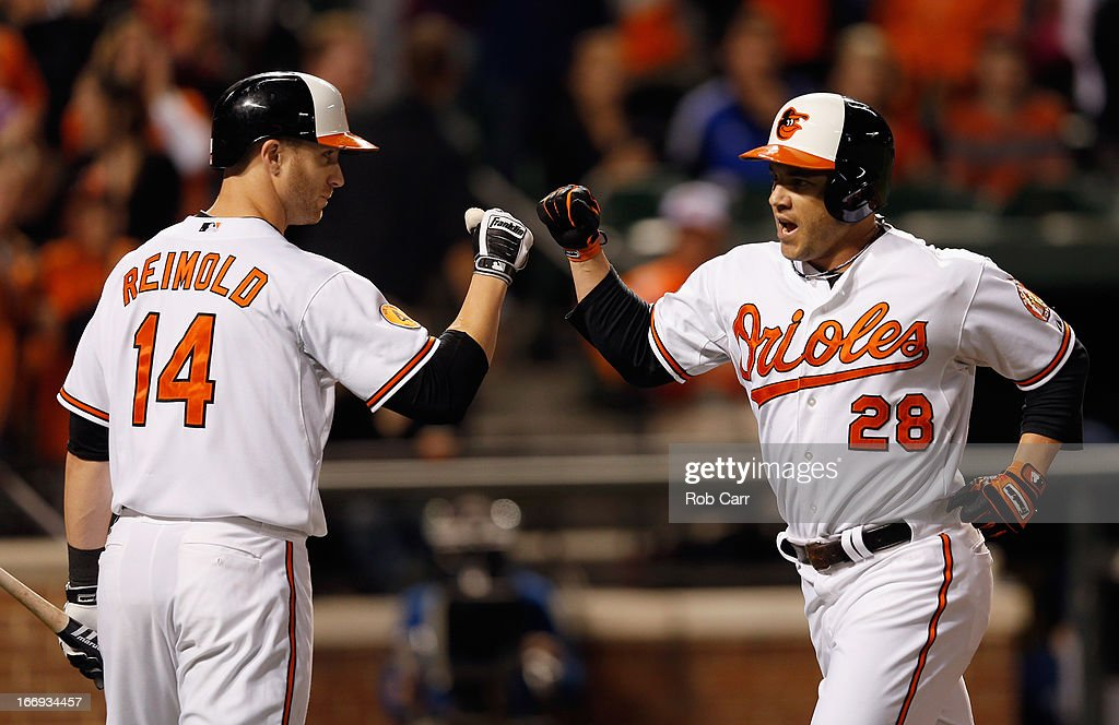 Steve Pearce #28 of the Baltimore Orioles celebrates with Nolan Reimold #14 after hitting a two RBI home run against the Tampa Bay Rays during the seventh inning of the Orioles 10-6 win at Oriole Park at Camden Yards on April 18, 2013 in Baltimore, Maryland.