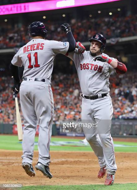 Steve Pearce of the Boston Red Sox celebrates with Rafael Devers after hitting a solo home run in the sixth inning against the Houston Astros during...