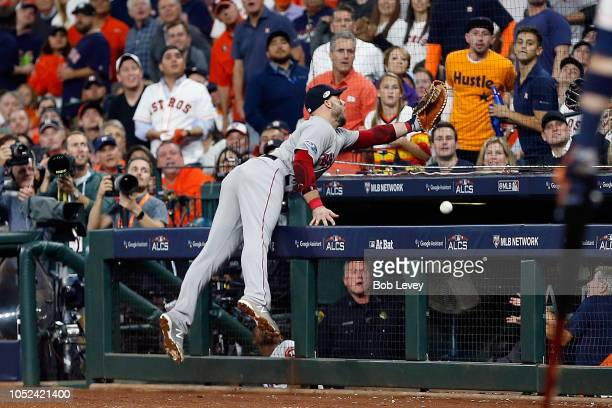 Steve Pearce of the Boston Red Sox falls into the Houston Astros dugout as he attempts to catch a foul ball hit by Josh Reddick of the Houston Astros...