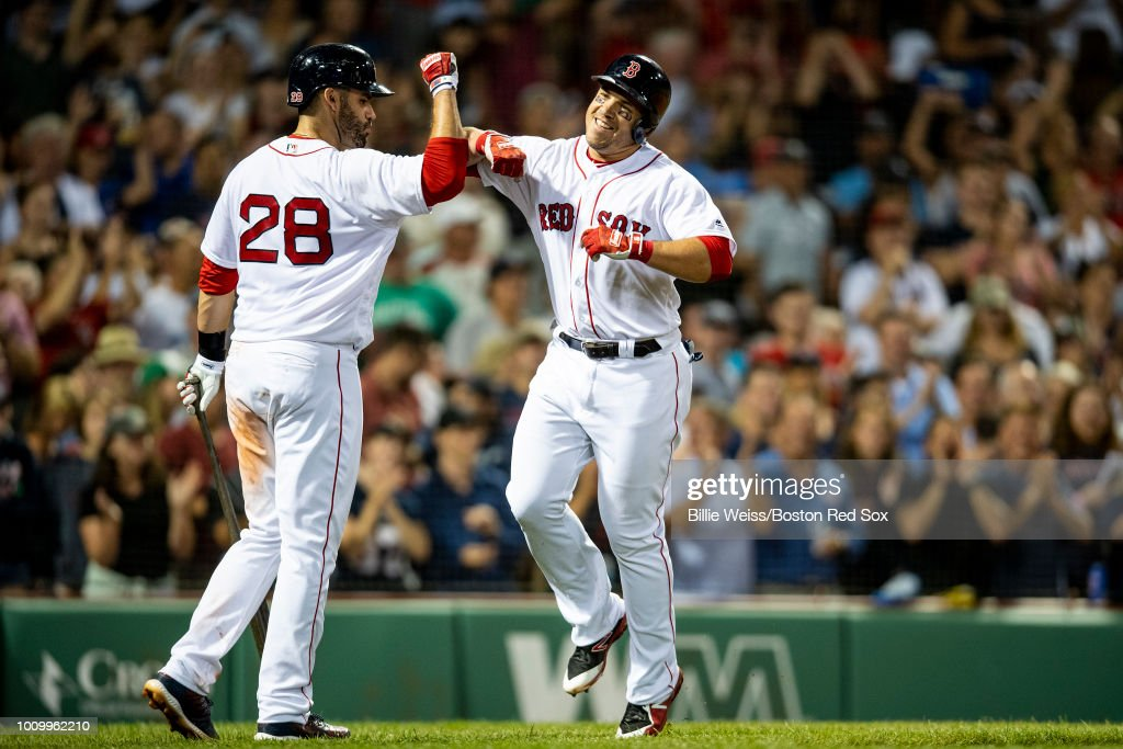 Steve Pearce #25 of the Boston Red Sox high fives J.D. Martinez #28 after hitting a two-run home run during the sixth inning of a game against the New York Yankees on August 2, 2018 at Fenway Park in Boston, Massachusetts. It was his third home run of the game.