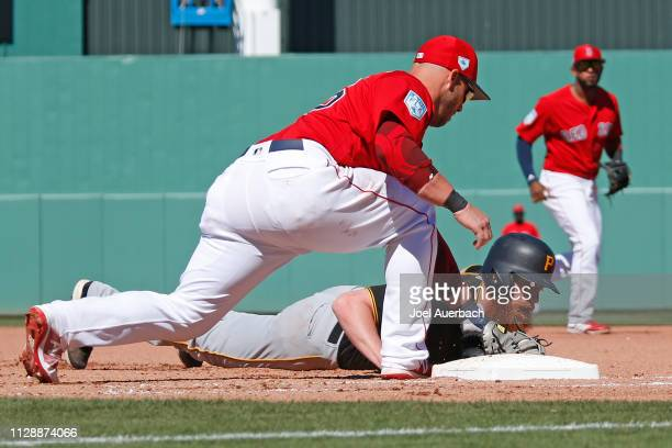 Steve Pearce of the Boston Red Sox tags out Colin Moran of the Pittsburgh Pirates after he took to big a lead off first base during a spring training...