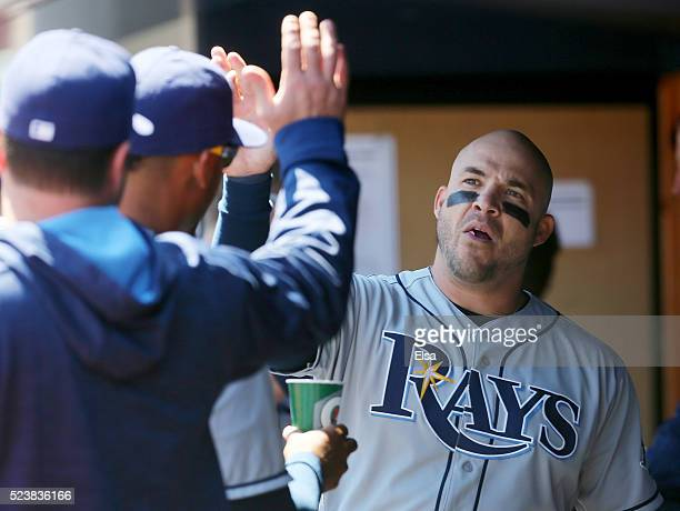 Steve Pearce of the Tampa Bay Rays is congratulated by teammates in the dugout after he scored in the first inning against the New York Yankees at...