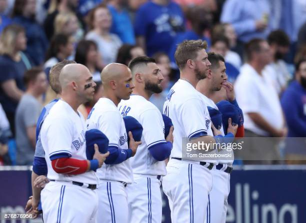 Steve Pearce of the Toronto Blue Jays and Ryan Goins and Kevin Pillar and Justin Smoak and Troy Tulowitzki stand for the playing of the anthems...
