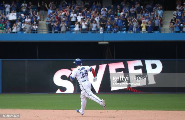Steve Pearce of the Toronto Blue Jays circles the bases after hitting a grand slam home run in the tenth inning during MLB game action against the...