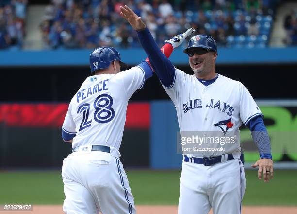 Steve Pearce of the Toronto Blue Jays is congratulated by first base coach Derek Shelton as he rounds the bases after hitting a gamewinning grand...