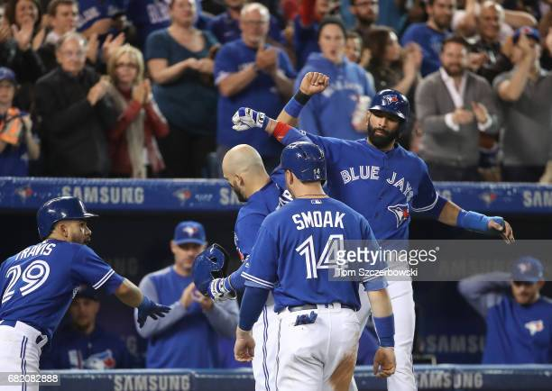 Steve Pearce of the Toronto Blue Jays is congratulated by Jose Bautista after hitting a threerun home run in the fifth inning during MLB game action...