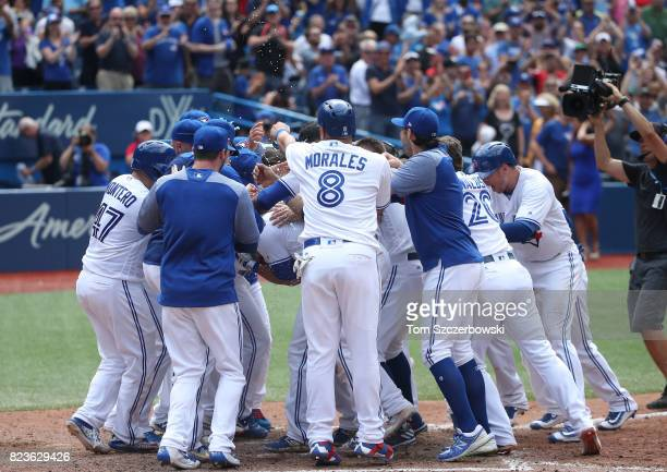 Steve Pearce of the Toronto Blue Jays is congratulated by teammates at home plate after hitting a gamewinning grand slam home run in the tenth inning...