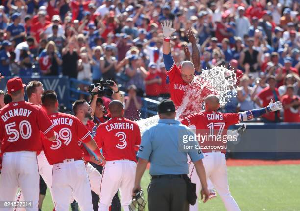 Steve Pearce of the Toronto Blue Jays is congratulated by teammates at home plate after hitting a gamewinning grand slam home run in the ninth inning...