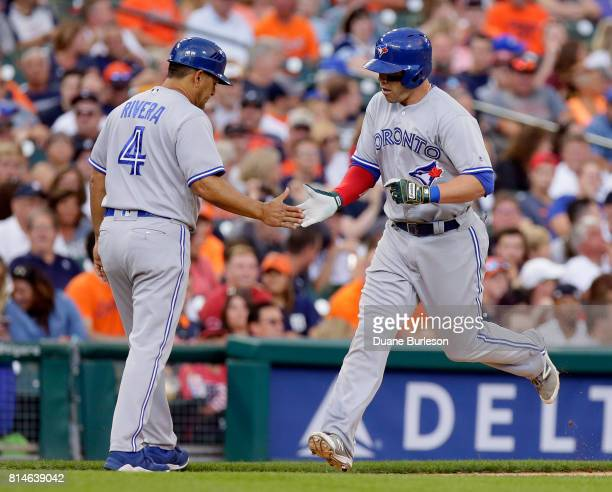 Steve Pearce of the Toronto Blue Jays is congratulated by third base coach Luis Rivera of the Toronto Blue Jays after hitting a solo home run against...