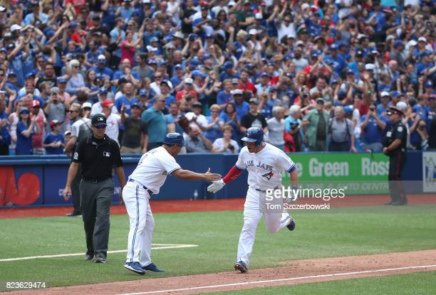 Steve Pearce of the Toronto Blue Jays is congratulated by third base coach Luis Rivera as he rounds the bases after hitting a gamewinning grand slam...