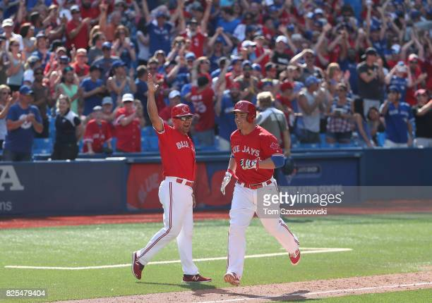Steve Pearce of the Toronto Blue Jays is congratulated by third base coach Luis Rivera after hitting a gamewinning grand slam home run in the ninth...