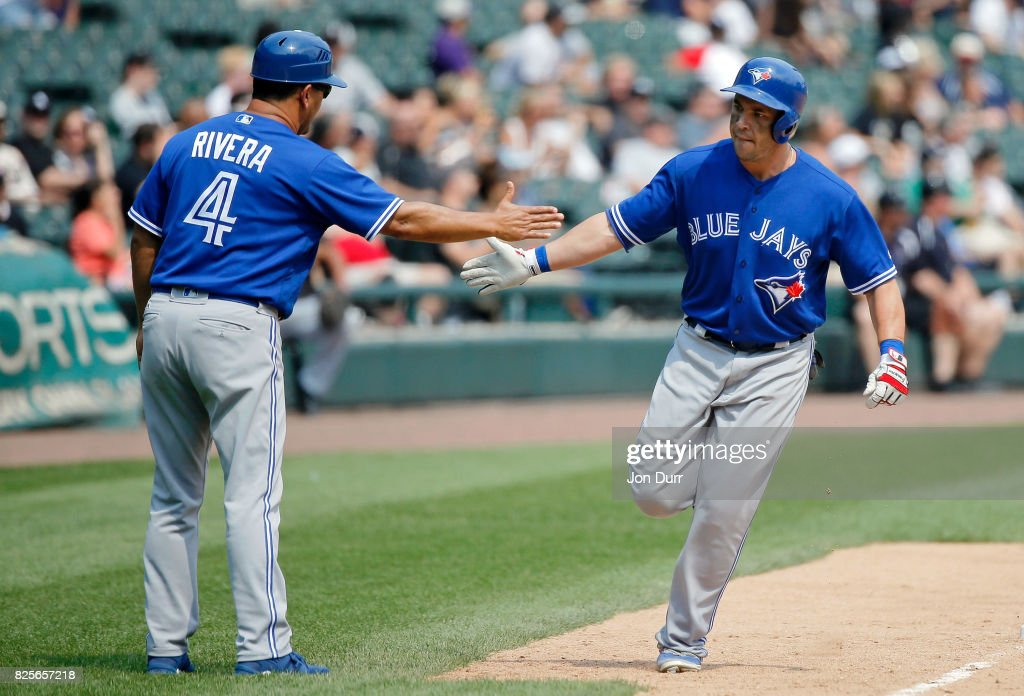 Steve Pearce #28 of the Toronto Blue Jays is congratulated by third base coach Luis Rivera #4 after hitting a home run against the Chicago White Sox during the sixth inning at Guaranteed Rate Field on August 2, 2017 in Chicago, Illinois.