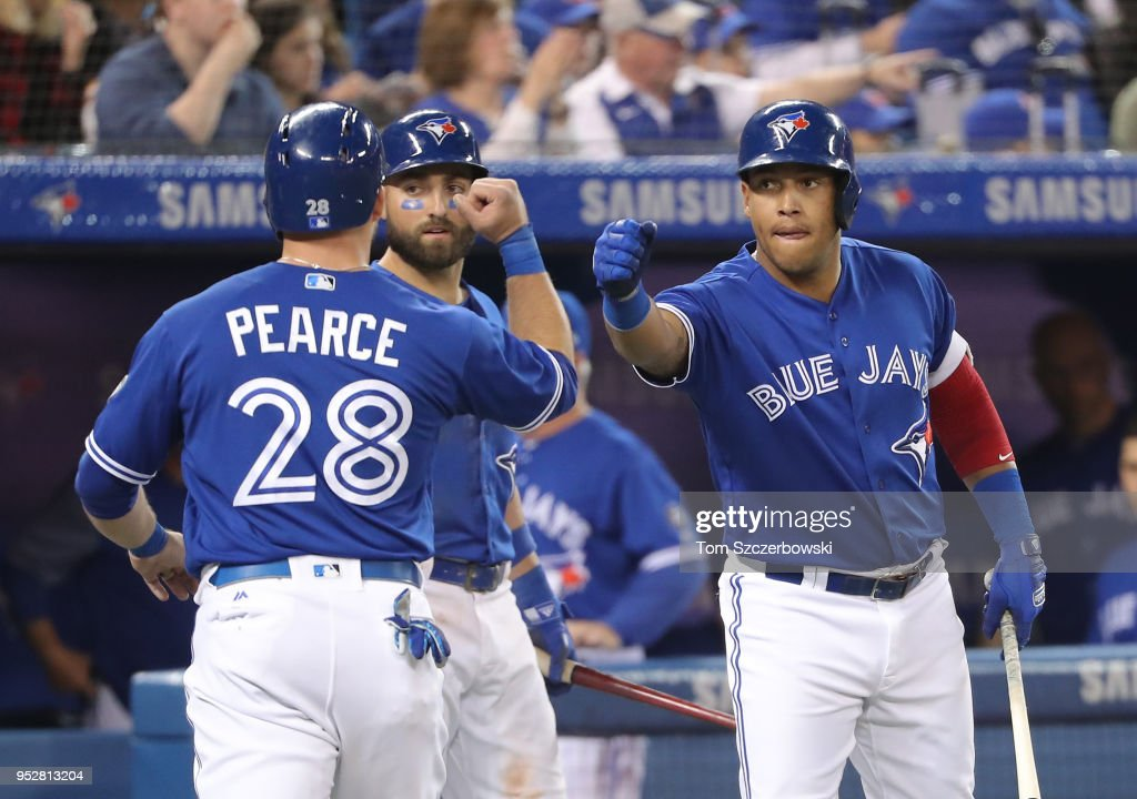 Steve Pearce #28 of the Toronto Blue Jays is congratulated by Yangervis Solarte #26 and Kevin Pillar #11 after scoring a run in the seventh inning during MLB game action against the Texas Rangers at Rogers Centre on April 29, 2018 in Toronto, Canada.