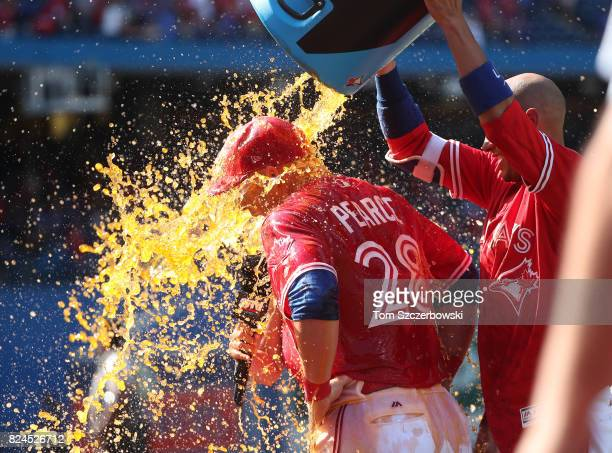 Steve Pearce of the Toronto Blue Jays is doused with a water cooler sports drink by Ryan Goins after hitting a gamewinning grand slam home run in the...