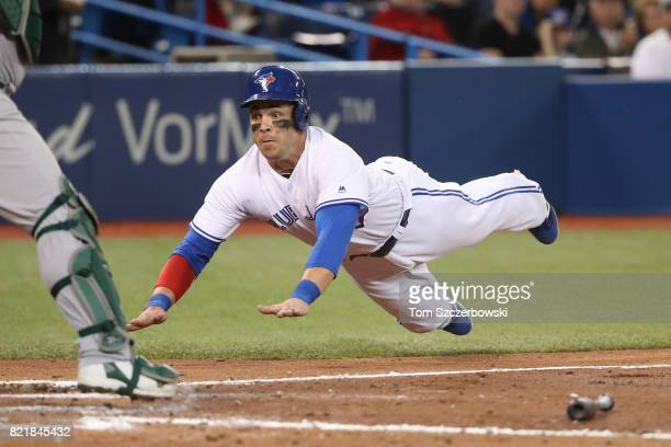 Steve Pearce of the Toronto Blue Jays is thrown out at home plate as he slides in the sixth inning during MLB game action against the Oakland...