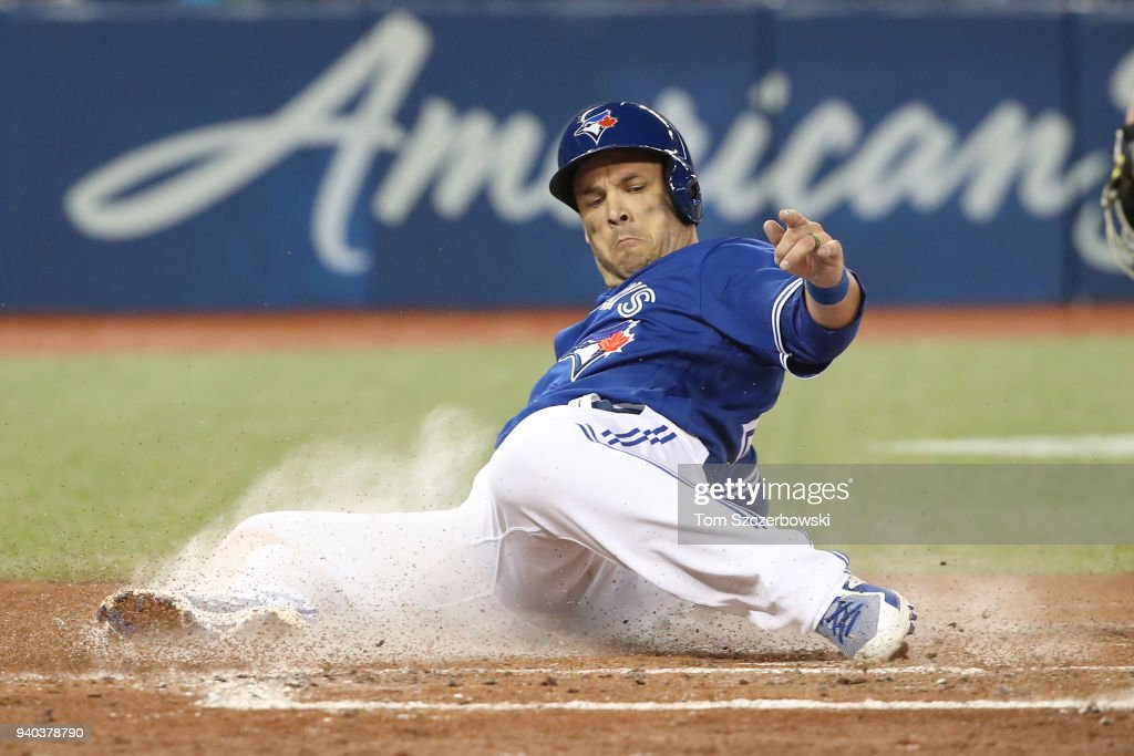 Steve Pearce #28 of the Toronto Blue Jays slides across home plate to score a run in the third inning during MLB game action against the New York Yankees at Rogers Centre on March 31, 2018 in Toronto, Canada.