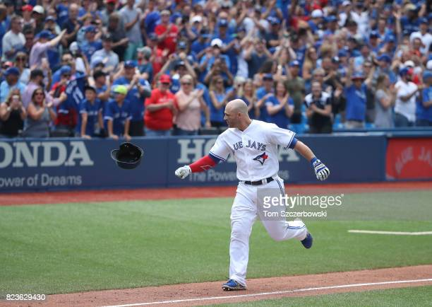 Steve Pearce of the Toronto Blue Jays tosses his helmet as he rounds the bases after hitting a gamewinning grand slam home run in the tenth inning...