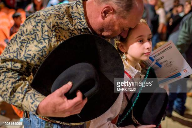 Steve Petrosky bows his head with his daughter Savannah Petrosky while the national anthem plays during the Houston Livestock Show and Rodeo on March...