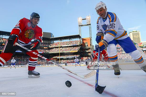 Steve Poapst of the Chicago Blackhawks and Peter Stastny of the St Louis Blues chase the puck during the 2017 NHL Winter Classic Alumni Game at Busch...