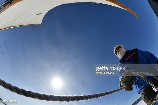 Steve Schwartz holds a rope as he sails his ice boat on a frozen Hudson River March 7 2014 in Barrytown New York These historic 'ice yachts' some...