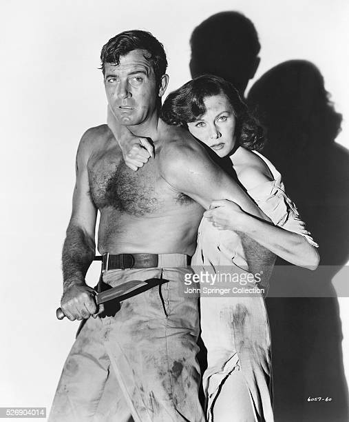 Steve Singleton protects Katherine Shelley holding her behind him in a scene from the 1951 adventure Crosswinds