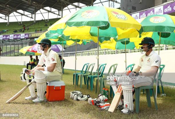 Steve Smith and David Warner of Australia look on as they wait to bat during day four of the First Test match between Bangladesh and Australia at...